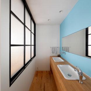 大阪の北欧スタイルのおしゃれな浴室 (フラットパネル扉のキャビネット、中間色木目調キャビネット、青い壁、無垢フローリング、オーバーカウンターシンク、木製洗面台、茶色い床、ブラウンの洗面カウンター) の写真