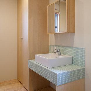 Modelo de cuarto de baño de estilo zen con paredes blancas, lavabo sobreencimera, baldosas y/o azulejos azules, baldosas y/o azulejos en mosaico, suelo de madera clara y encimera de azulejos