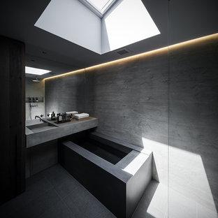 Modelo de cuarto de baño urbano con jacuzzi, ducha abierta, baldosas y/o azulejos grises, baldosas y/o azulejos de piedra, lavabo integrado, encimera de cemento y ducha abierta
