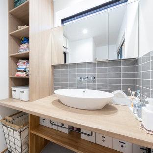 他の地域のアジアンスタイルのおしゃれなバスルーム (浴槽なし) (オープンシェルフ、淡色木目調キャビネット、グレーのタイル、サブウェイタイル、白い壁、ベッセル式洗面器、木製洗面台、グレーの床、ベージュのカウンター) の写真