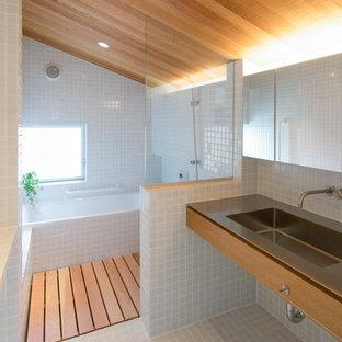 Свежая идея для дизайна: маленькая главная ванная комната в восточном стиле с открытыми фасадами, серыми фасадами, полновстраиваемой ванной, душем без бортиков, белой плиткой, плиткой мозаикой, белыми стенами, полом из мозаичной плитки, врезной раковиной, столешницей из нержавеющей стали, белым полом, шторкой для ванной, серой столешницей, тумбой под одну раковину, напольной тумбой и деревянным потолком - отличное фото интерьера