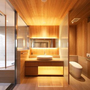 Imagen de cuarto de baño asiático con armarios con paneles lisos, puertas de armario de madera oscura, sanitario de una pieza, paredes marrones, lavabo sobreencimera y suelo beige