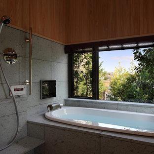 東京都下のコンテンポラリースタイルのおしゃれなマスターバスルーム (ドロップイン型浴槽、石タイル、オープン型シャワー、グレーの壁、グレーの床、オープンシャワー) の写真