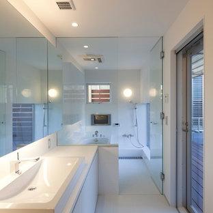Cette photo montre une grand salle de bain principale tendance avec un placard à porte plane, des portes de placard blanches, une baignoire d'angle, un espace douche bain, un carrelage blanc, des carreaux de porcelaine, un mur blanc, un sol en carrelage de porcelaine, une vasque, un plan de toilette en surface solide, un sol blanc, aucune cabine et un plan de toilette blanc.