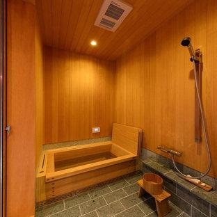 Inspiration för ett orientaliskt badrum, med en kantlös dusch, grå kakel, bruna väggar och ett japanskt badkar