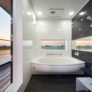 他の地域の小さいモダンスタイルのおしゃれな浴室 (黒い床、ドロップイン型浴槽、オープン型シャワー、マルチカラーの壁、オープンシャワー) の写真