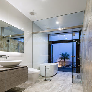 Immagine di una stanza da bagno padronale design con ante lisce, ante grigie, vasca freestanding, zona vasca/doccia separata, WC monopezzo, piastrelle beige, pareti grigie, lavabo a bacinella, pavimento grigio, doccia aperta e top beige