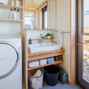 他の地域のコンテンポラリースタイルのおしゃれなバスルーム (浴槽なし) (白い壁、オーバーカウンターシンク、木製洗面台、グレーの床) の写真
