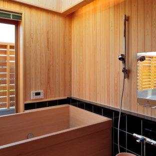 他の地域, の和風のおしゃれなマスターバスルーム (和式浴槽、黒いタイル、ベージュの壁) の写真