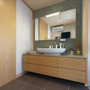 Asiatisches Badezimmer mit flächenbündigen Schrankfronten, hellbraunen Holzschränken, weißer Wandfarbe, Aufsatzwaschbecken und schwarzem Boden in Sonstige