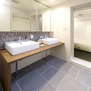 Ejemplo de cuarto de baño de estilo zen con armarios con paneles lisos, paredes blancas, lavabo sobreencimera, suelo de baldosas de cerámica, encimera de madera, baldosas y/o azulejos en mosaico y encimeras marrones