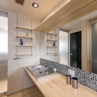 東京都下のコンテンポラリースタイルのおしゃれな浴室 (青いタイル、白い壁、淡色無垢フローリング、オーバーカウンターシンク、茶色い床) の写真