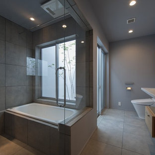 Photo of a modern ensuite bathroom in Tokyo with flat-panel cabinets, light wood cabinets, a built-in bath, a double shower, a one-piece toilet, grey tiles, grey walls, a wall-mounted sink, grey floors, an open shower, ceramic flooring and white worktops.