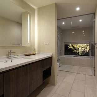 他の地域のモダンスタイルのおしゃれなマスターバスルーム (フラットパネル扉のキャビネット、茶色いキャビネット、一体型トイレ、ベージュのタイル、ベージュの壁、磁器タイルの床、アンダーカウンター洗面器、人工大理石カウンター、ベージュの床、白い洗面カウンター) の写真