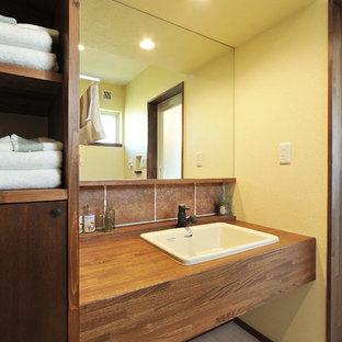 他の地域のアジアンスタイルのおしゃれな浴室 (オープンシェルフ、黄色い壁、オーバーカウンターシンク、ベージュの床) の写真