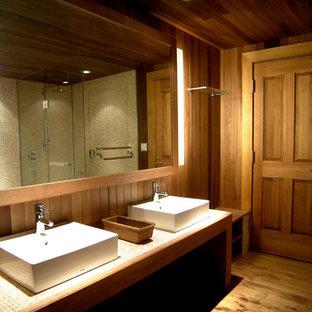 Esempio di una grande stanza da bagno padronale tradizionale con vasca idromassaggio, doccia alcova, pistrelle in bianco e nero, piastrelle di vetro, pareti marroni, pavimento in compensato, lavabo da incasso, top piastrellato, pavimento marrone e porta doccia a battente