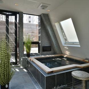 東京23区のインダストリアルスタイルのおしゃれな浴室 (大型浴槽、モノトーンのタイル、白い壁、磁器タイルの床、グレーの床) の写真