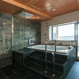 トラディショナルスタイルのおしゃれなマスターバスルーム (ドロップイン型浴槽、洗い場付きシャワー、マルチカラーのタイル、マルチカラーの壁、黒い床) の写真