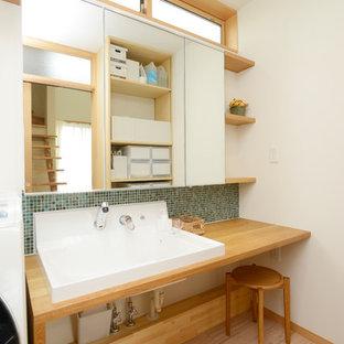 Modelo de cuarto de baño escandinavo con paredes blancas, suelo de madera pintada, encimera de madera, suelo marrón y encimeras marrones