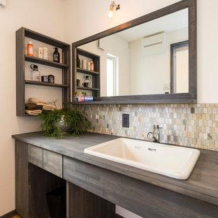 他の地域のコンテンポラリースタイルのおしゃれな浴室 (フラットパネル扉のキャビネット、白い壁、無垢フローリング、オーバーカウンターシンク、茶色い床、濃色木目調キャビネット) の写真