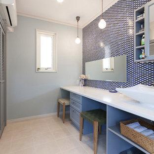 名古屋のトランジショナルスタイルのおしゃれな浴室 (落し込みパネル扉のキャビネット、青いキャビネット、青いタイル、青い壁、ベッセル式洗面器、ベージュの床、白い洗面カウンター) の写真