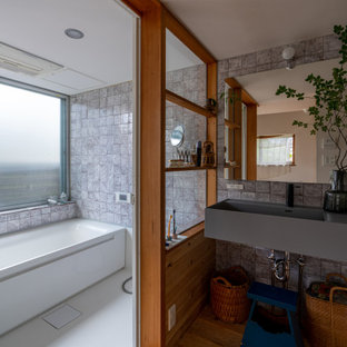 他の地域のアジアンスタイルのおしゃれな浴室 (アルコーブ型浴槽、洗い場付きシャワー、グレーのタイル、無垢フローリング、壁付け型シンク、茶色い床) の写真