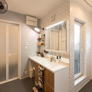 京都のインダストリアルスタイルのおしゃれな浴室 (フラットパネル扉のキャビネット、中間色木目調キャビネット、白いタイル、マルチカラーの壁、一体型シンク、グレーの床) の写真