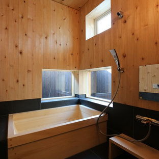 Inspiration for an asian bathroom in Other with a freestanding tub, an open shower, brown walls, black floor and an open shower.