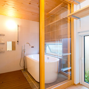 Foto di una stanza da bagno design con vasca freestanding, doccia aperta, piastrelle bianche, pareti grigie, pavimento grigio e doccia aperta