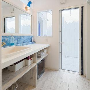 他の地域のビーチスタイルのおしゃれな浴室 (オープンシェルフ、淡色木目調キャビネット、青いタイル、モザイクタイル、白い壁、オーバーカウンターシンク、ベージュの床、白い洗面カウンター) の写真