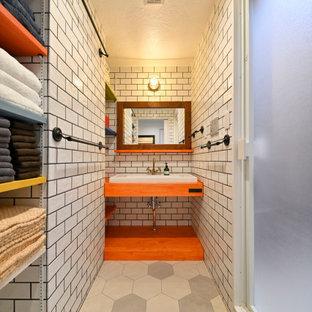 他の地域の中くらいのアジアンスタイルのおしゃれなバスルーム (浴槽なし) (オープンシェルフ、グレーのタイル、サブウェイタイル、ベッセル式洗面器、グレーの床、オレンジの洗面カウンター、洗面台1つ、造り付け洗面台) の写真