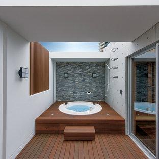 広いモダンスタイルのおしゃれな浴室 (大型浴槽、グレーのタイル) の写真