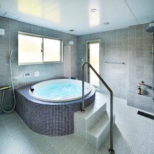 東京都下の広いヴィクトリアン調のおしゃれなマスターバスルーム (大型浴槽、オープン型シャワー、グレーのタイル、ライムストーンタイル、グレーの壁、ライムストーンの洗面台、開き戸のシャワー、グレーの洗面カウンター) の写真