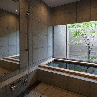 Inspiration för ett orientaliskt badrum, med ett japanskt badkar, grå väggar, en kantlös dusch, grå kakel, keramikplattor och klinkergolv i keramik