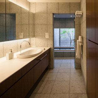 Удачное сочетание для дизайна помещения: ванная комната в восточном стиле с темными деревянными фасадами, серыми стенами, накладной раковиной и серой плиткой - самое интересное для вас