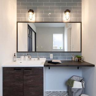 他の地域の中くらいのコンテンポラリースタイルのおしゃれなバスルーム (浴槽なし) (フラットパネル扉のキャビネット、グレーのタイル、サブウェイタイル、白い壁、一体型シンク、グレーの床、白い洗面カウンター、洗面台1つ、造り付け洗面台) の写真