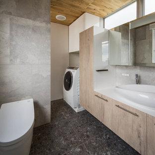 大阪のインダストリアルスタイルのおしゃれな浴室 (フラットパネル扉のキャビネット、淡色木目調キャビネット、グレーの壁、黒い床) の写真