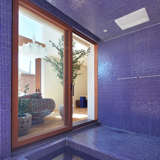 Tuscan blue tile blue floor drop-in bathtub photo in Osaka with blue walls