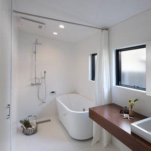 東京23区のモダンスタイルのおしゃれなマスターバスルーム (置き型浴槽、バリアフリー、白い壁、オーバーカウンターシンク、ベージュの床、シャワーカーテン、ブラウンの洗面カウンター) の写真