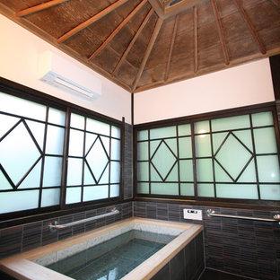 他の地域の和風のおしゃれな浴室 (コーナー型浴槽、白い壁、黒い床) の写真