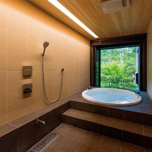 Asiatisches Badezimmer mit Whirlpool, beigefarbenen Fliesen, Porzellanfliesen, beiger Wandfarbe, Porzellan-Bodenfliesen und schwarzem Boden