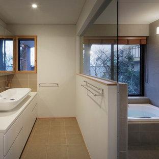 東京23区の大きいモダンスタイルのおしゃれな浴室 (フラットパネル扉のキャビネット、白いキャビネット、ドロップイン型浴槽、洗い場付きシャワー、一体型トイレ、グレーのタイル、セラミックタイル、白い壁、セラミックタイルの床、ベッセル式洗面器、人工大理石カウンター、ベージュの床、オープンシャワー、白い洗面カウンター) の写真