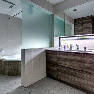 Modelo de cuarto de baño contemporáneo con armarios con paneles lisos, puertas de armario grises, bañera esquinera, ducha abierta, paredes grises, lavabo integrado, suelo gris y ducha abierta