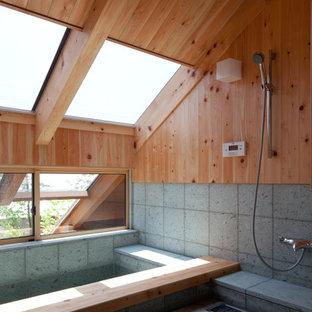 Modelo de cuarto de baño asiático con suelo verde, bañera esquinera, ducha abierta, paredes marrones y ducha abierta
