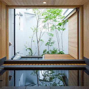 Ejemplo de cuarto de baño minimalista con bañera esquinera y paredes marrones