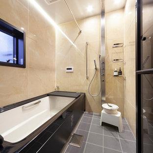 他の地域のコンテンポラリースタイルのおしゃれな浴室 (シャワー付き浴槽、ベージュの壁、グレーの床、ベージュのタイル) の写真