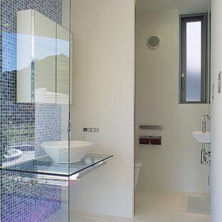 他の地域, のモダンスタイルのおしゃれな浴室 (青いタイル、ベッセル式洗面器、ガラスの洗面台、白い床) の写真