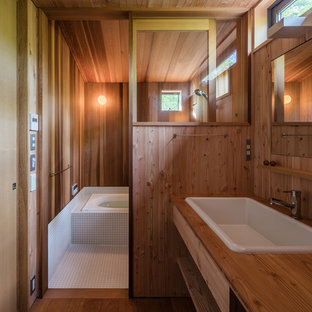 他の地域の中くらいの北欧スタイルのおしゃれな浴室 (オープンシェルフ、茶色い壁、無垢フローリング、オーバーカウンターシンク、木製洗面台、茶色い床) の写真