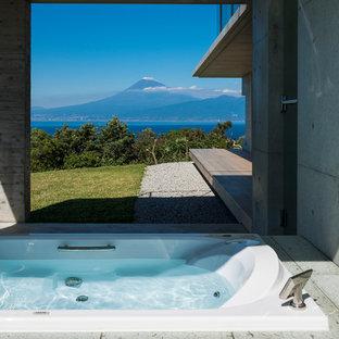 Modelo de cuarto de baño contemporáneo con bañera encastrada y paredes grises