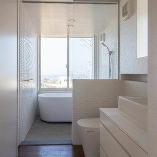 他の地域のビーチスタイルのおしゃれな浴室 (フラットパネル扉のキャビネット、白いキャビネット、置き型浴槽、一体型トイレ、白い壁、濃色無垢フローリング、ベッセル式洗面器、オープンシャワー、段差なし、白いタイル、茶色い床) の写真